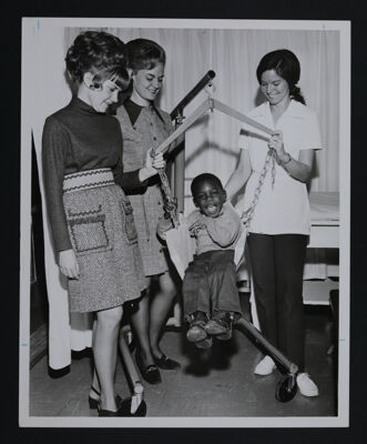 Alumnae with Child Using Therapy Equipment Photograph, c. 1970