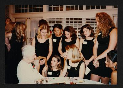 Collegians Around Alumna in White Dress Photograph, 1997